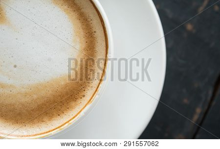 Flatlay Half Heart Shape Froth Milk Latte Art in White Coffee Cup on Black Wood Table. Heart shape froth milk Latte art hot beverage for coffee lover poster