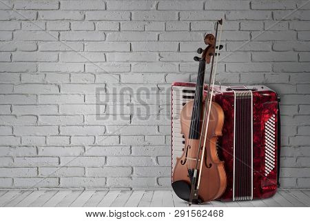Vintage Red Accordion And Violin On Brick Wall Background