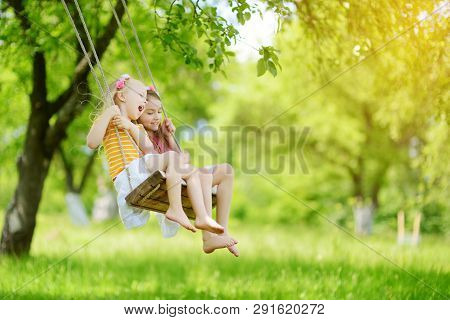 Two Cute Little Sisters Having Fun On A Swing Together In Beautiful Summer Garden On Warm And Sunny