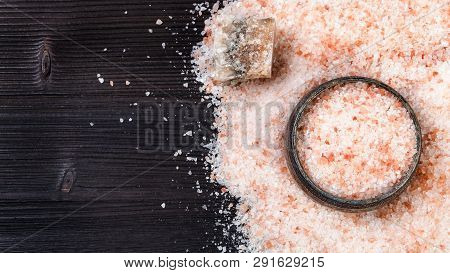 Top View Of Silver Salt Cellar, Raw Natural Pink Halite Mineral And Grained Himalayan Salt On Dark B