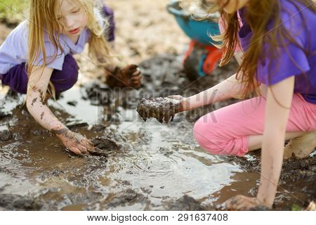 Two Funny Little Girls Playing In A Large Wet Mud Puddle On Sunny Summer Day. Children Getting Dirty