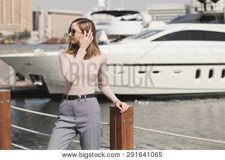 Young European Female Standing Near Big Yacht. Woman In A Beige Turtleneck And Trousers, Casual Or S