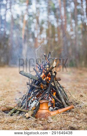 At The Stake In The Spring Forest, A Clay Turkish Coffee Pot Is Heated Against The Grass.