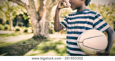 Boy using asthma inhaler in the park on a sunny day
