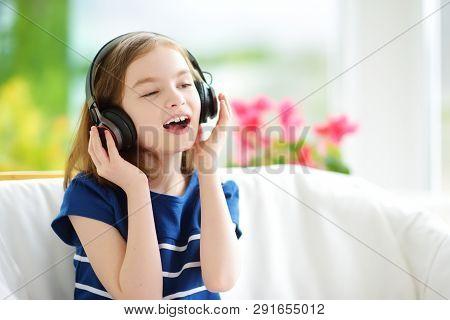 Cute Little Girl Wearing Huge Wireless Headphones. Pretty Child Listening To The Music. Schoolgirl H