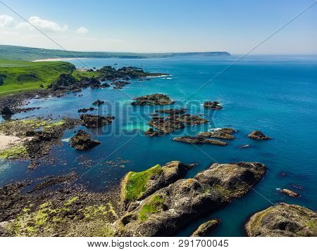 Vivid Emerald-green Water At Ballintoy Harbour Along The Causeway Coast In County Antrim. Rugged Coa