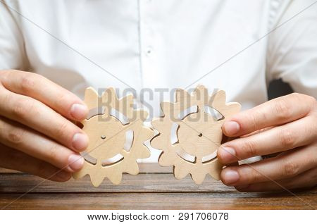 Businessman In White Shirt Connects Two Wooden Gears. Symbolism Of Establishing Business Processes A