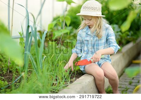 Adorable Little Girl Wearing Straw Hat Playing With Her Toy Garden Tools In A Greenhouse On Sunny Su