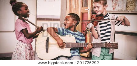 Smiling children playing musical instruments in classroom at school