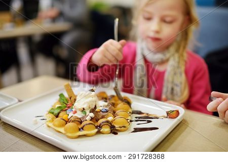 Adorable Little Girl Eating Bubble Waffle With Fruits, Chocolate And Marshmallows. Children Eating S