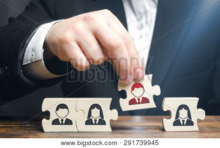 A Businessman Collects Puzzles Symbolizing A Team Of Employees. The Concept Of Creating A Business T