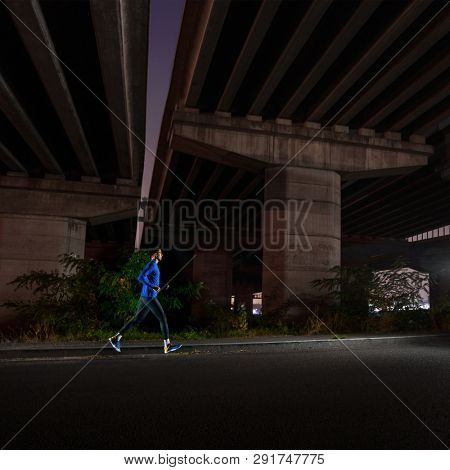 Young Man in Blue Running Outside at Night. Urban Running. Healthy Lifestyle and Sport Concept.