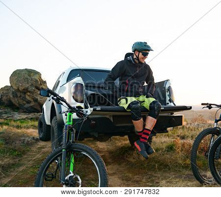 Smiling Cyclist Resting on the Pickup Off Road Truck after Enduro Bike Riding in the Mountains and Talking with Friends. MTB Adventure and Car Travel Concept.