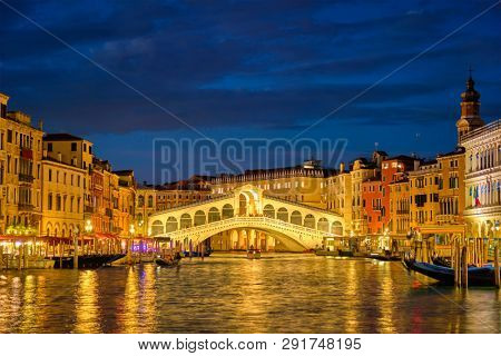 Famous Venetian tourist landmark Rialto bridge (Ponte di Rialto) over Grand Canal illuminated at night in Venice, Italy