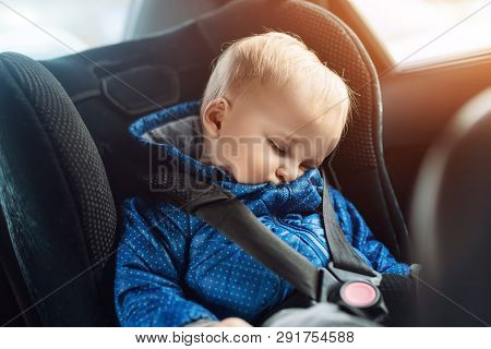 Cute Caucasian Toddler Boy Sleeping In Child Safety Seat In Car During Road Trip. Adorable Baby Drea