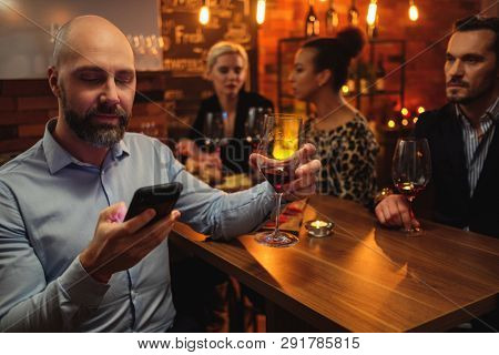 Man with cell phone behind bar counter in a cafe