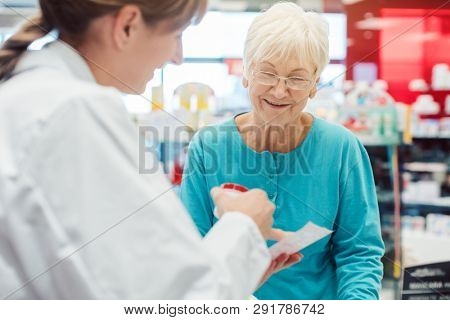 Senior woman in pharmacy talking to the chemist or pharmacist explain effects of a drug