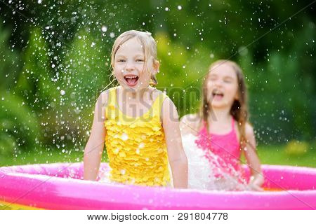 Adorable Little Girls Playing In Inflatable Baby Pool. Happy Kids Splashing In Colorful Garden Play