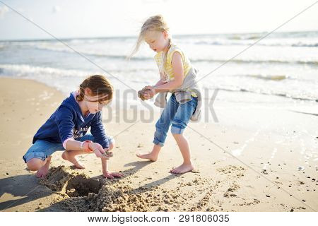 Two Little Sisters Having Fun On A Sandy Beach On Warm And Sunny Summer Day. Kids Playing By The Oce