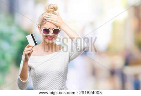 Young beautiful blonde woman holding credit card over isolated background stressed with hand on head, shocked with shame and surprise face, angry and frustrated. Fear and upset for mistake.
