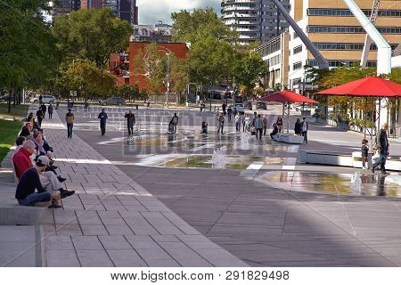 Montreal, Quebec, Canada, September 29, 2018: People Rest Near The Fountains On The Des Arts Section