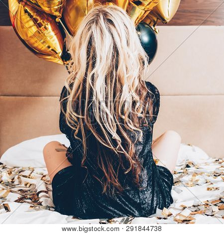 Fashion Model Image. Party Leisure Time. Blonde Female In Black Sitting On Bed Backview. Balloons An