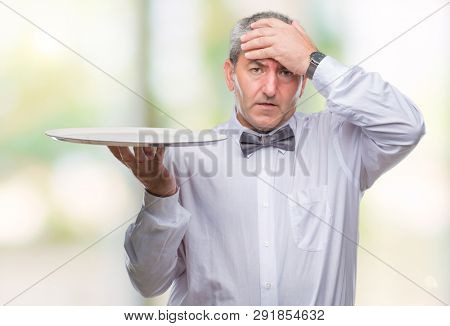 Handsome senior waiter man holding silver tray over isolated background stressed with hand on head, shocked with shame and surprise face, angry and frustrated. Fear and upset for mistake.
