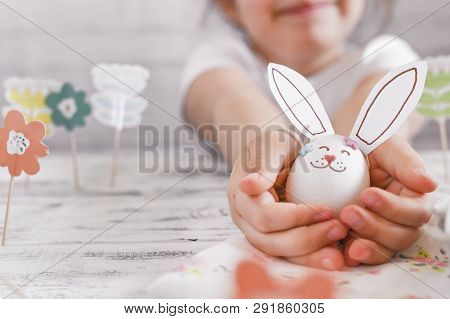 Little Girl With Bunny Ears And Easter Decoration And Eggs On A White Background. The Hands Of The C