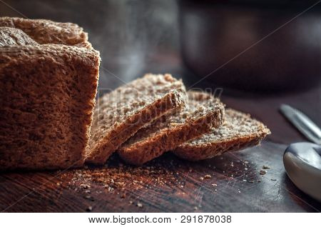 Closeup Of Fresh Homemade Organic Whole Grain Bread With Crispy Crust And Warm Steam Cut Into Slices