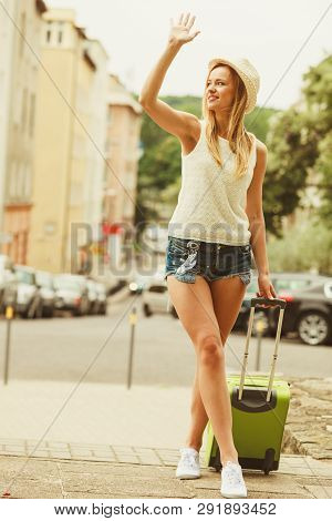 Hitch Hiking And Travelling. Lovely Smiling Cute Girl With Green Suitcase Luggage Baggage Waiting Fo