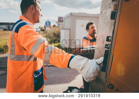 Two refuse collection workers loading garbage into waste truck emptying containers