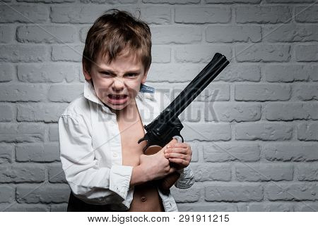 Angry Little Boy In White Shirt Holding Long Revolver Gun On Brick Wall Backdrop
