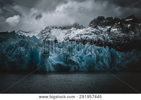 Vibrant Blue Ice In Front Of Snowy Mountains Taken At Grey Glacier In Torres Del Paine National Park
