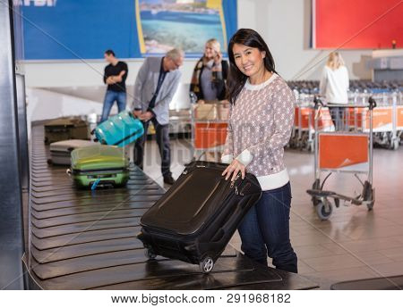 Smiling Woman Collecting Luggage At Conveyor Belt In Airport