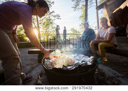 Woman Grilling Food On Skewers With Friends In Background