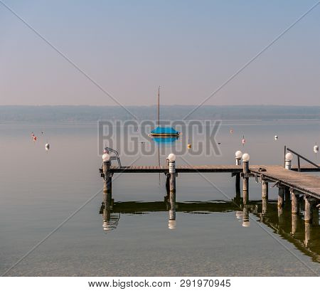 Image Of Mothballed Sailing Boat On A Lake With Wodden Private Pier In The Foreground