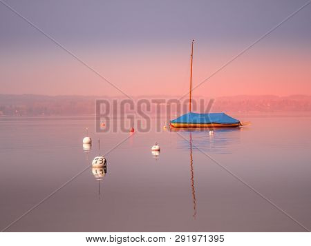 Image Of Mothballed Sailing Boat On A Lake With Water Reflections During Sunset
