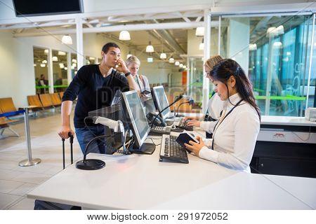 Staff Examining Passport While Passengers Waiting In Airport