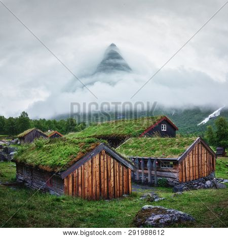 Norwegian old wooden fishing houses with grass roofs in Innerdalen - Norway's most beautiful mountains valley, near Innerdalsvatna lake. Norway, Europe