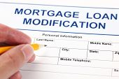 Mortgage Loan Modification application form and human hand with pencil. poster