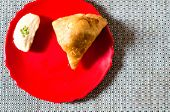 Samosa, peda barfi on red plate and woven mat, typical indian snack breakfast poster