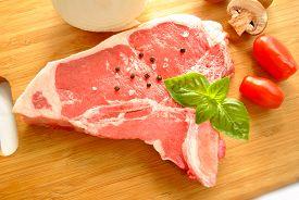 Raw Pork Chop With Fresh Ingredients On A Cutting Board