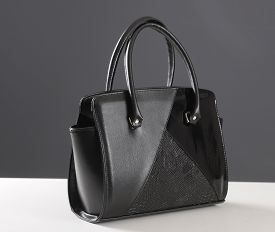 Elegant Reptile Leather Black Women Bag On White Table And Gray Background