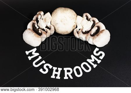 A Few White Champignons. Some Of Them Are Cut Into Slices. The Inscription At The Bottom Of Mushroom