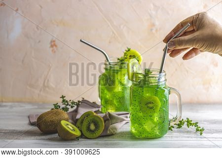 Woman Hand Holding Drinking Straw Over Glass Jar Of Kiwi Juice Or Smoothie. Kiwi Mojito Cocktail Or