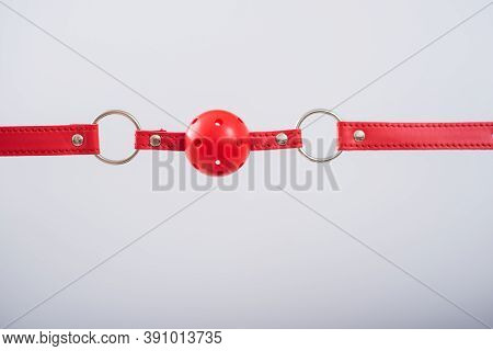 Close-up Of A Red Bdsm Gag On A White Background