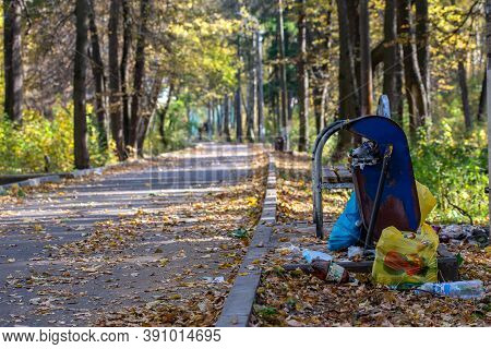 Tula, Russia - October 4, 2020: Overflowing Trash Can In Lost Park At Daylight In Early Autumn.