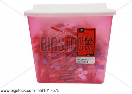 Lake Forest, CA. / USA - October 22, 2020: Used Needle Container. A full Used Hypodermic Needle container. Isolated on white. Room text. Editorial.
