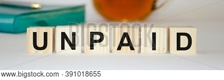 The Unpaid Word Is Written On A Wooden Block. Unpaid Text On Wooden Cubes, Notepad And Tea In The Ba