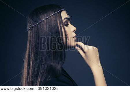 Young fashion woman with long straight brown hairs on dark background